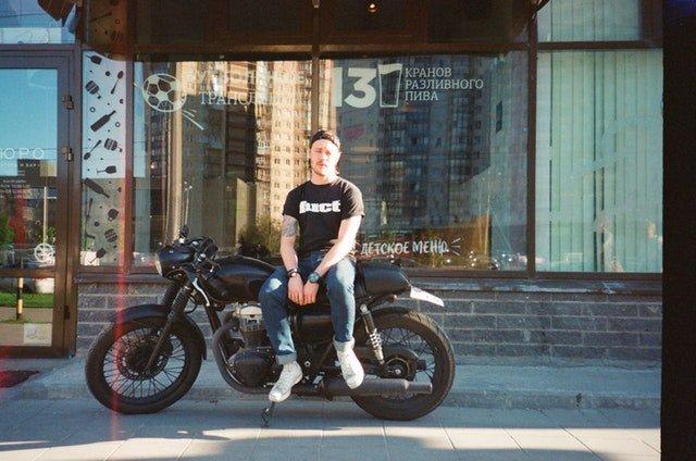 Muž sedí na motorke pred presklenou krčmou.jpg