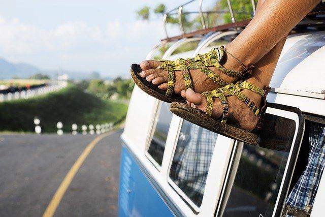 Ženské nohy v sandáloch na streche auta.jpg