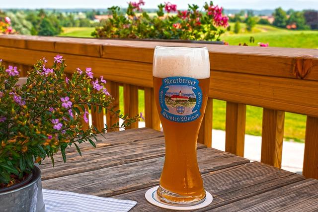 Pivo a kvet na drevenom stole na balkóne pri drevenom zábradlí.jpg